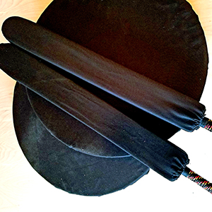 two black foam swords on top of two black round shields on white background