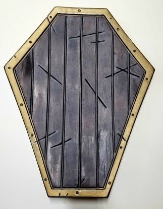 gold rimmed coffin shaped wooden shield
